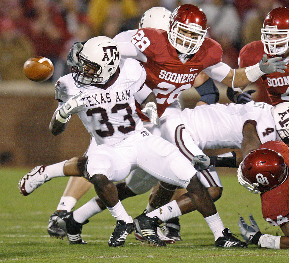 Photo - OU's Travis Lewis grabs Texas A&M's Christine Michael as he fumbles the ball during the Big 12 college football game between the University of Oklahoma Sooners and the Texas A&M Aggies at Gaylord Family - Oklahoma Memorial Stadium in Norman, Okla., Saturday, November 14, 2009.  Oklahoma recovered the fumble for a touchdown on the play Photo by Bryan Terry, The Oklahoman
