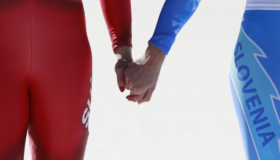 Photo - Women's downhill gold medal winners Switzerland's Dominique Gisin, left, and Slovenia's Tina Maze, right, hold hands on the podium during a flower ceremony at the Sochi 2014 Winter Olympics, Wednesday, Feb. 12, 2014, in Krasnaya Polyana, Russia.(AP Photo/Gero Breloer)
