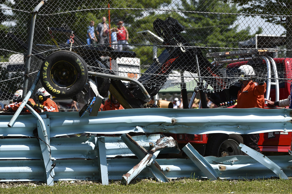Photo - Wreckage from the race car of Michael McDowell (95) protrudes through the catch fence during a NASCAR Sprint Cup Series auto race at Watkins Glen International, Sunday, Aug. 10, 2014, in Watkins Glen N.Y. The crash and resulting damage to the protective barriers resulted in race stoppage for over an hour. (AP Photo/Derik Hamilton)