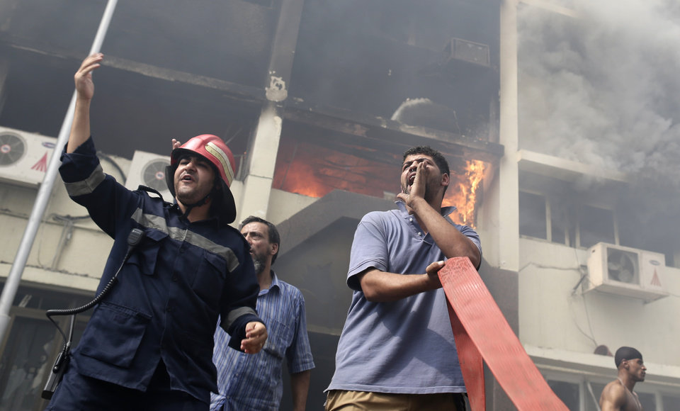 Photo - Egyptian firefighters battle flames at the Giza governorate buildings that were stormed and torched by angry supporters of Egypt's ousted president, Cairo, Egypt, Thursday, Aug. 15, 2013. Egypt faced a new phase of uncertainty on Thursday after the bloodiest day since its Arab Spring began, with hundreds of people reported killed and thousands injured as police smashed two protest camps of supporters of the deposed Islamist president. Wednesday's raids touched off day-long street violence that prompted the military-backed interim leaders to impose a state of emergency and curfew, and drew widespread condemnation from the Muslim world and the West, including the United States. (AP Photo/Hassan Ammar)