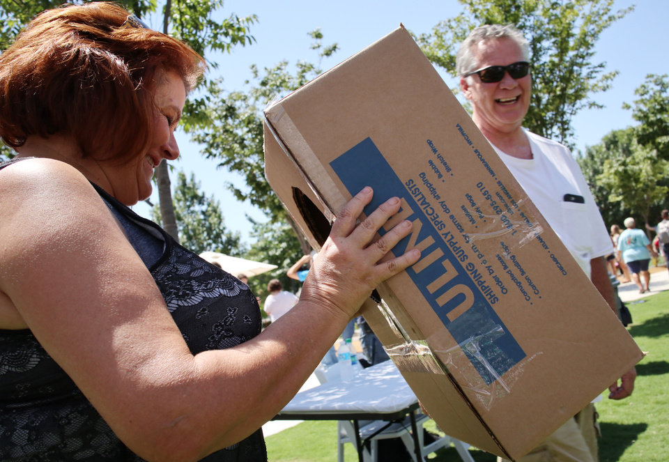 Photo - Pamm Tucker borrows a box set up to view the eclipse while Steve Short watches, during the great American solar eclipse party on the Great Lawn of the Myriad Botanical Gardens Monday, August 21, 2017. Photo by Doug Hoke, The Oklahoman