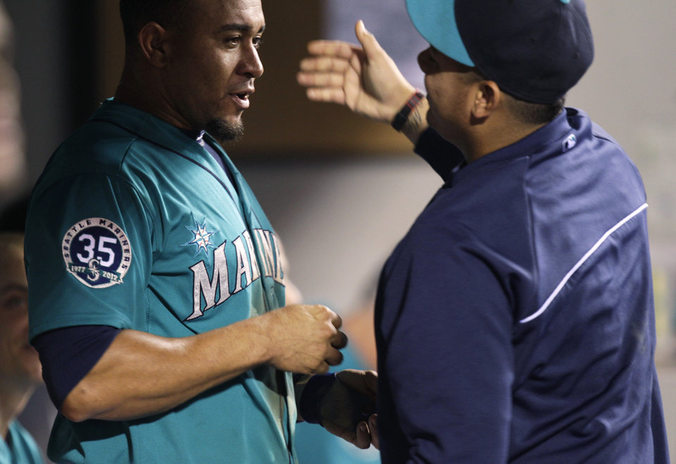 Photo -   Seattle Mariners' Miguel Olivo, left, gets a dugout hug from Mariners pitcher Felix Hernandez, right, after Olivo hit a two-run home run in the eighth inning to give the Mariners a 6-3 win over the Texas Rangers, Friday, Sept. 21, 2012, in Seattle. (AP Photo/Ted S. Warren)