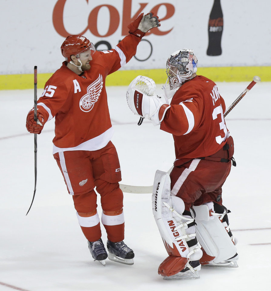 Photo - Detroit Red Wings goalie Jimmy Howard (35) is congratulated by teammate Niklas Kronwall (55), of Sweden, after their 3-2 win over the Los Angeles Kings during the shootout period of an NHL hockey game in Detroit, Saturday, Jan. 18, 2014. (AP Photo/Carlos Osorio)