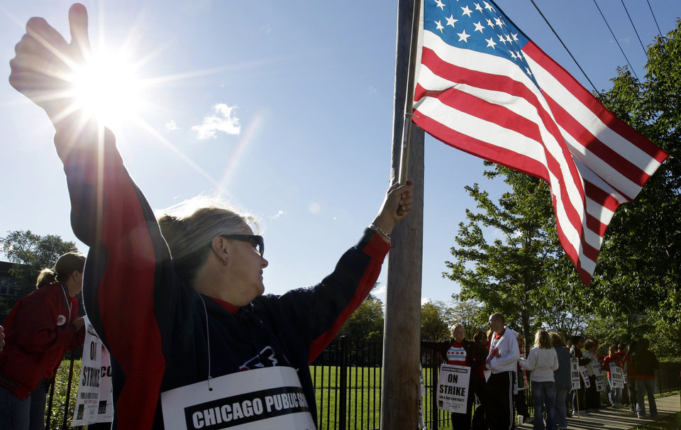 Photo -   Teacher Patty Westcott pickets outside Clissold Elementary School in Chicago, Tuesday, Sept. 18, 2012, as a strike by the Chicago Teachers Union continues into its second week. CTU members in the nation's third-largest city will pore over the details of a contract settlement Tuesday as the clock ticks down to an afternoon meeting in which they are expected to vote on ending a seven-day strike that has kept 350,000 students out of class. (AP Photo/M. Spencer Green)