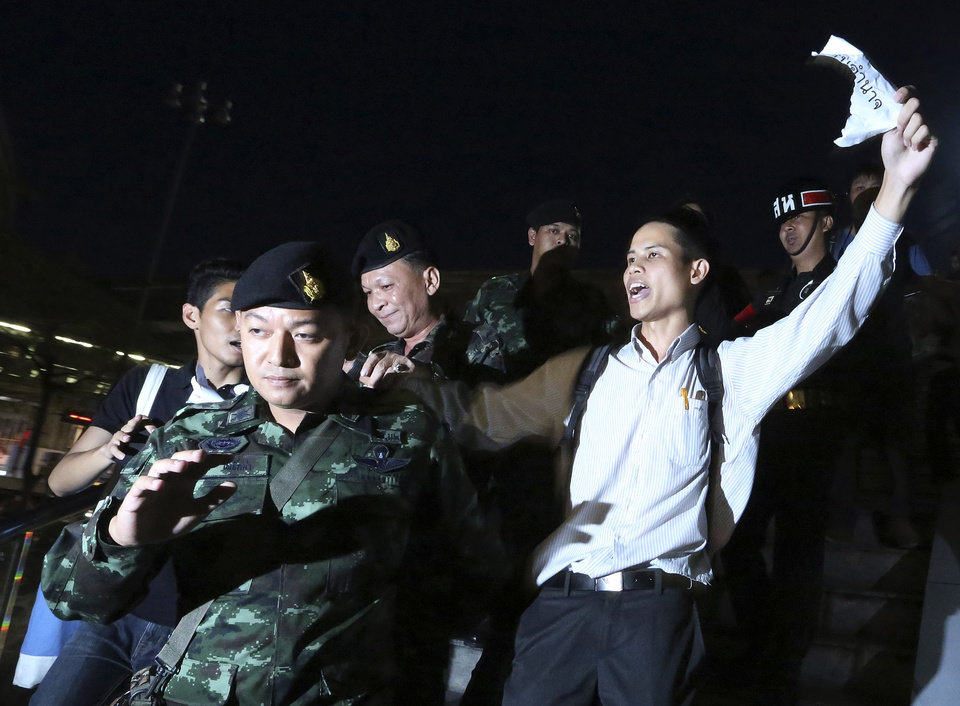 Photo - Thai soldiers detain Apichat Pongsawat, right, an activist who staged a protest against the coup in downtown Bangkok, Thailand Friday, May 23, 2014. Ousted members of Thailand's former government turned themselves in to the country's new military junta Friday, as soldiers forcefully dispersed hundreds of anti-coup activists who defied a ban on large-scale gatherings to protest the army's seizure of power. (AP Photo/Apichart Weerawong)