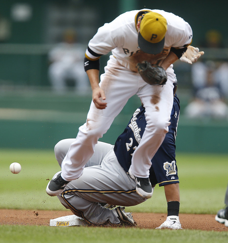 Photo - Pittsburgh Pirates shortstop Clint Barmes, top, hops as the ball gets away while Milwaukee Brewers' Carlos Gomez steal second base in the first inning of the baseball game on Sunday, June 30, 2013, in Pittsburgh. (AP Photo/Keith Srakocic)