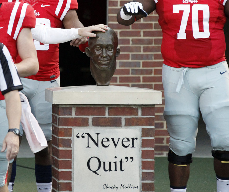 Photo - In this photo taken on Oct. 19, 2013, Mississippi players touch the bust of former defensive back Roy Lee