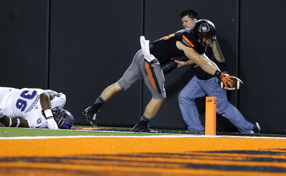 Photo - Oklahoma State's David Glidden (13) dives for a touchdown as Central Arkansas's Brandon Porter (36) tries to tackle him in the fourth quarter during the college football game between the Oklahoma State Cowboys (OSU) and the Central Arkansas Bears at Boone Pickens Stadium in Stillwater, Okla., Saturday, Sept. 12, 2015. Photo by Sarah Phipps, The Oklahoman