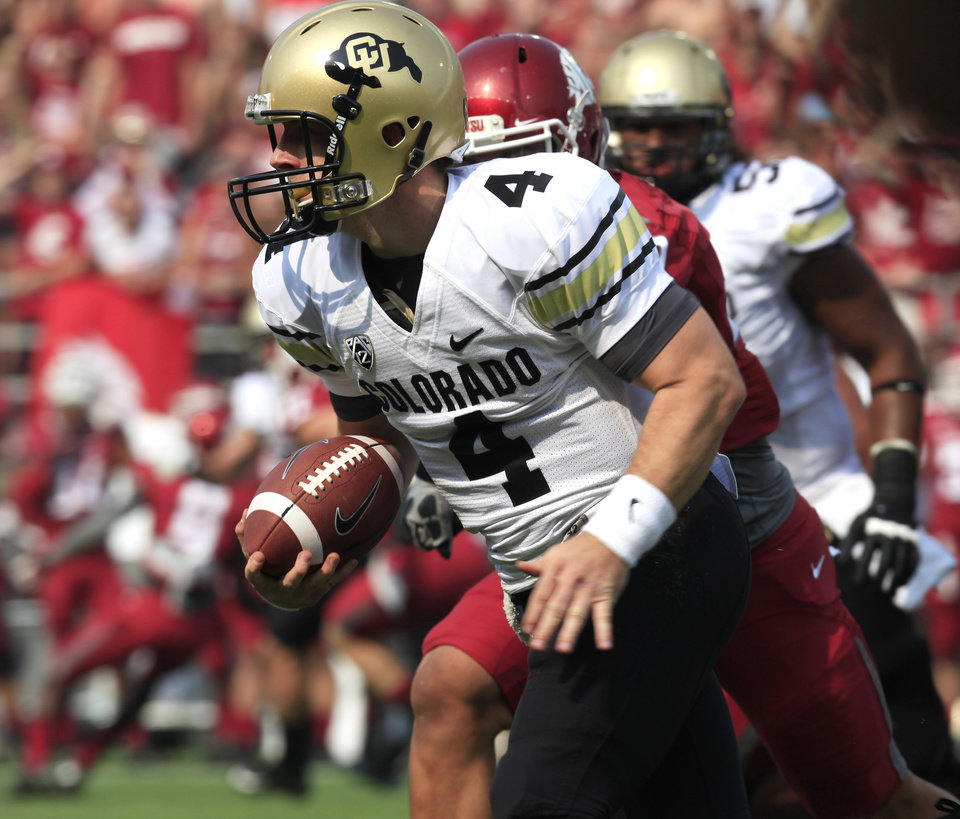 Photo -   Colorado quarterback Jordan Webb (4) scrambles to avoid the rush of Washington State linebacker Darryl Monroe, obscured, during the first quarter of an NCAA college football game Saturday, Sept. 22, 2012, at Martin Stadium in Pullman, Wash. (AP Photo/Dean Hare)