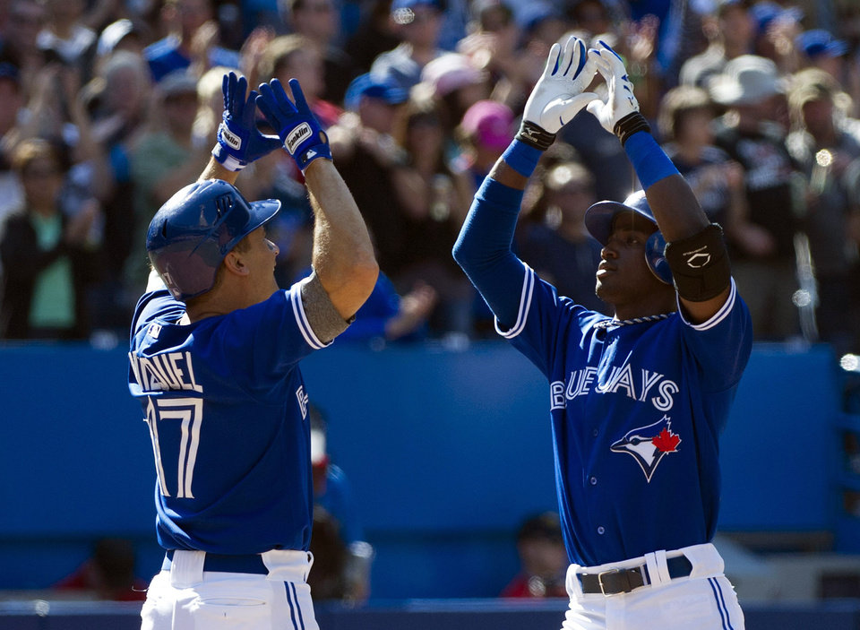 Photo -   Toronto Blue Jays' Adeiny Hechavarria, right, celebrates his two-run home run with teammate Omar Vizquel during seventh inning of a baseball game against the Boston Red Sox in Toronto on Sunday, Sept. 16, 2012. (AP Photo/The Canadian Press, Nathan Denette)