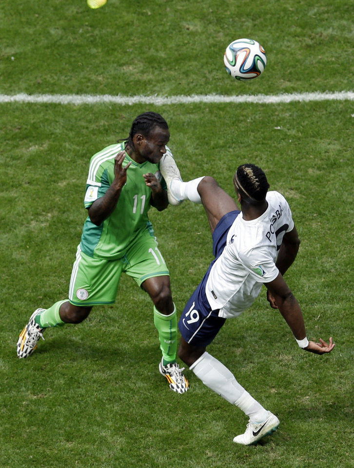 Photo - Nigeria's Victor Moses, left, and France's Paul Pogba challenge for the ball during the World Cup round of 16 soccer match between France and Nigeria at the Estadio Nacional in Brasilia, Brazil, Monday, June 30, 2014. (AP Photo/Hassan Ammar)