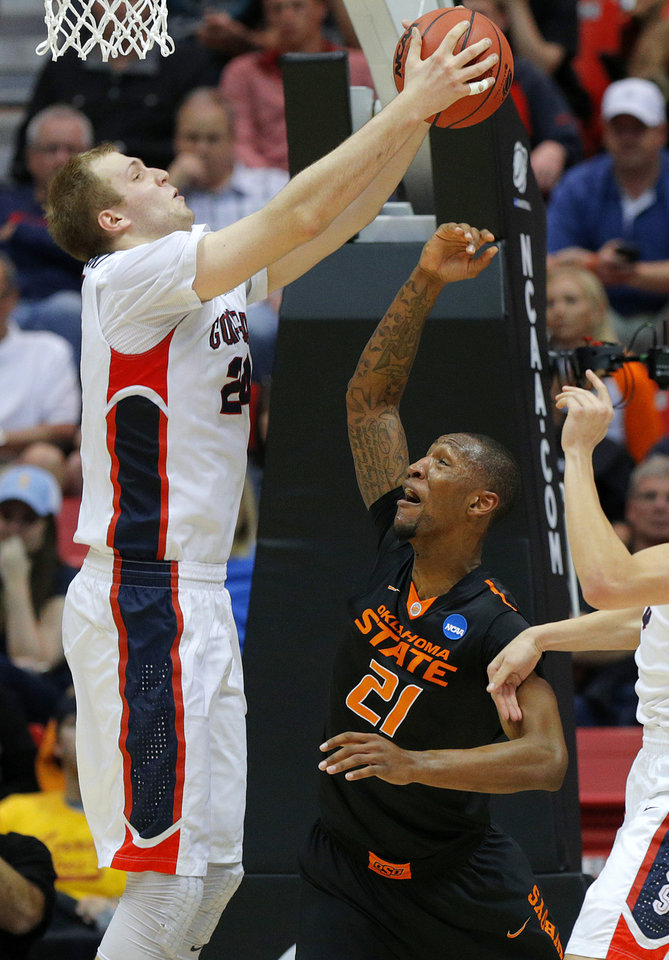 Photo - Gonzaga's Ryan Edwards (25) grabs a rebound over Oklahoma State's Kamari Murphy (21) during a second round game of the NCAA men's college basketball tournament at Viejas Arena in San Diego, between Oklahoma State and Gonzaga Friday, March 21, 2014. Gonzaga won 85-77. Photo by Bryan Terry, The Oklahoman
