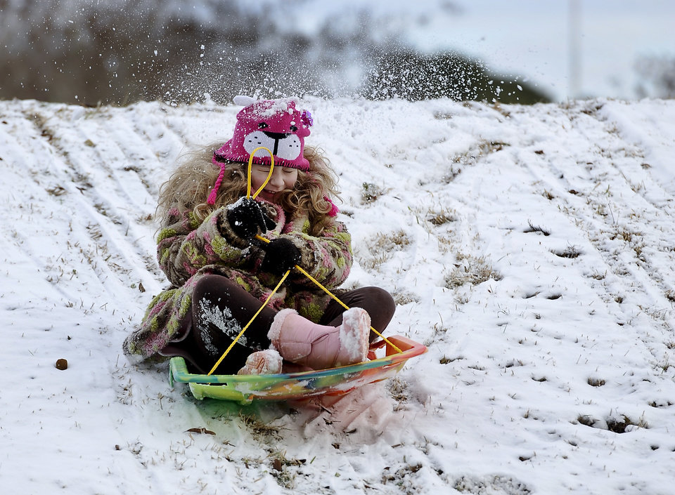 Photo - Hannah Wurtz, 9, gets a snowball in the back from her father, Gary Wurtz, not pictured, as she starts her sledding run Friday, Jan. 24, 2014, outside William R. Johnson Coliseum on the Stephen F. Austin State campus in Nacogdoches, Texas. A winter storm which moved across Texas on Thursday and into Friday dumped varying amounts of snow and caused school delays and cancellations across much of the region. (AP Photo/The Daily Sentinel, Andrew D. Brosig) MANDATORY CREDIT
