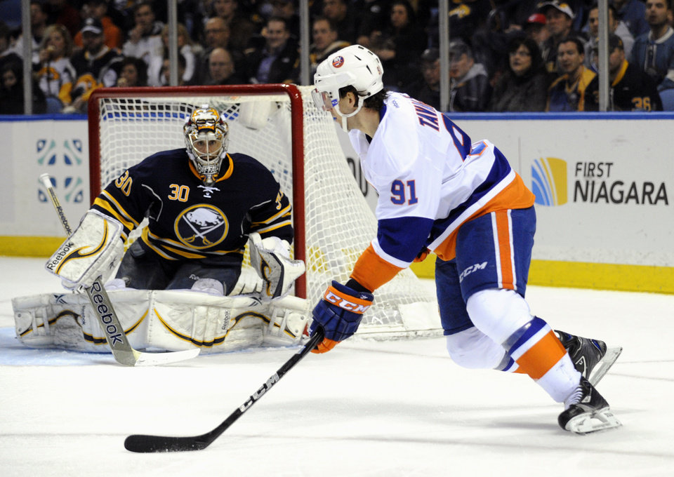 Buffalo Sabres' goaltender Ryan Miller eyes the puck as New York Islanders' center John Tavares (91) cuts in front of the goal during the second period of an NHL hockey game in Buffalo, N.Y., Saturday, Feb. 23, 2013. (AP Photo/Gary Wiepert)