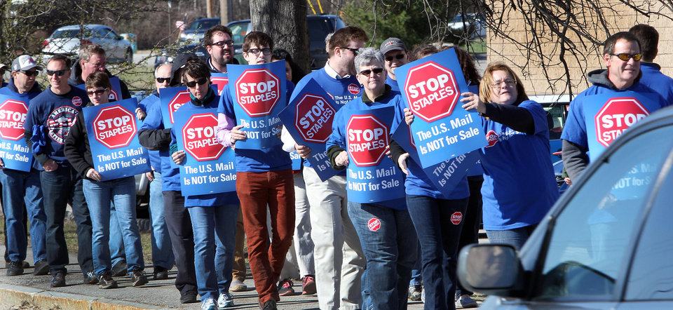 Photo - Postal workers picket in front of a Staples store Thursday April 24, 2014 in Concord, N.H.  Postal workers around the country protested in front of Staples stores, objecting to the U.S. Postal Service's pilot program to open counters in stores, staffed with retail employees. (AP Photo/Jim Cole)