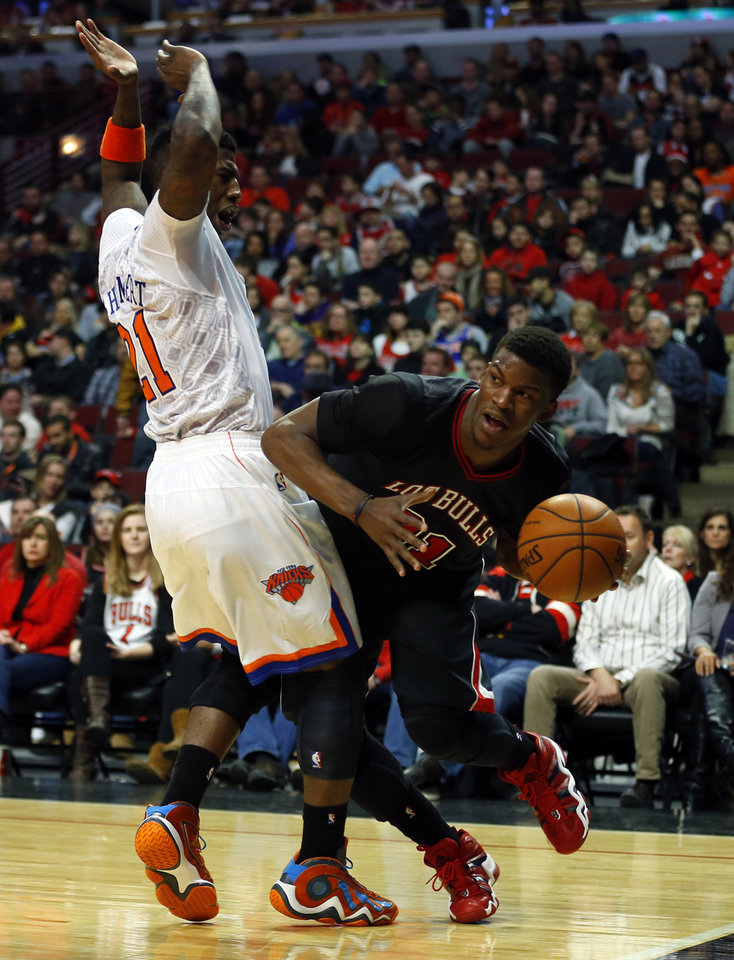 Photo - Chicago Bulls shooting guard Jimmy Butler, right, tries to get around New York Knicks shooting guard Iman Shumpert, left, during the second half of an NBA basketball game on Sunday, March 2, 2014, in Chicago. The Bulls won the game 109-90. (AP Photo/Jeff Haynes)
