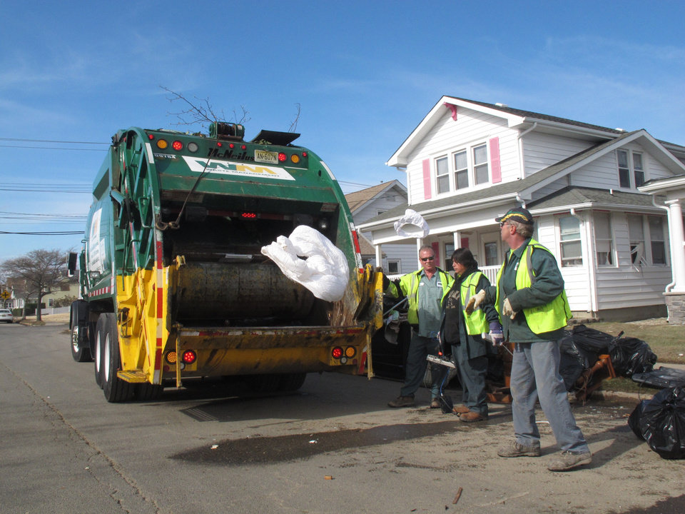 Photo - A Nov. 5, 2012 photo shows public works employees tossing waterlogged bedding into a garbage truck in Point Pleasant Beach N.J.   a week after Superstorm Sandy roared through. Debris disposal costs are a major expense for towns that were hard hit by the storm. Even with federal reimbursement for much of the cleanup and rebuilding expenses, these towns could be facing property tax hikes next year as a result of the unexpected costs, and the loss of millions of dollars of taxable property. (AP Photo/Wayne Parry)