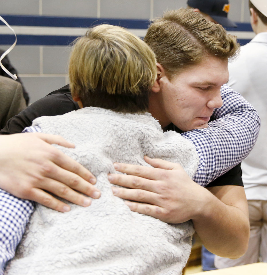Photo - Hunter Richard gets a hug from Barbara Hinckley, the mother of one of his friends, after Richard signed to attend Army West Point where he will play football, during a ceremony for National Signing Day at Edmond North High School in Edmond, Okla., Wednesday, Feb. 7, 2018. Photo by Nate Billings, The Oklahoman