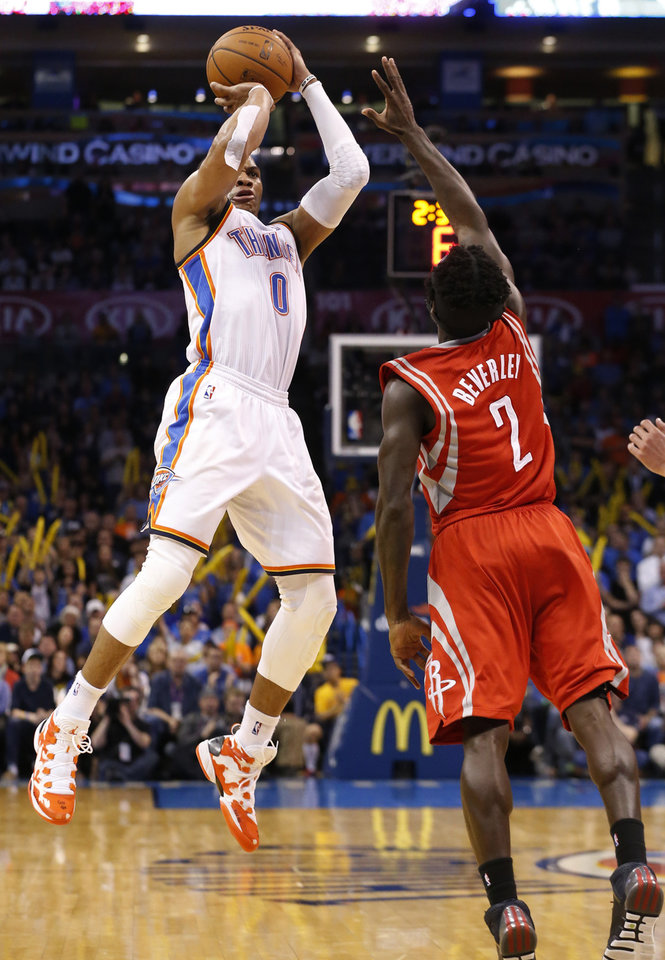 Photo - Oklahoma City Thunder guard Russell Westbrook (0) shoots over Houston Rockets guard Pat Beverley (2) during the fourth quarter of an NBA basketball game in Oklahoma City, Tuesday, March 11, 2014. Oklahoma City won 106-98. (AP Photo/Sue Ogrocki)