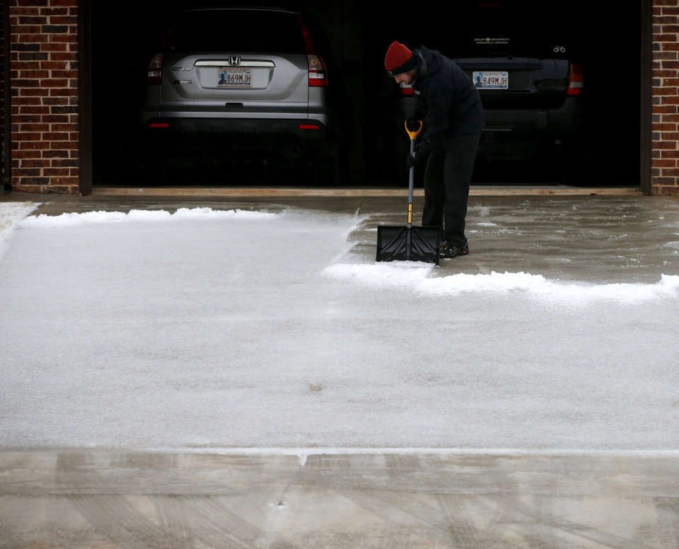 Photo - Garett Brown shovels sleet off his driveway in northwest Oklahoma City, Sunday, December 27, 2015. Photo by Bryan Terry, The Oklahoman