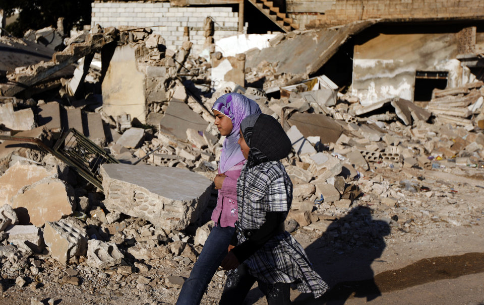 Photo -   FILE - In this Tuesday, June 5, 2012 file photo, Syrian girls walk by the rubble of a house which was destroyed during a military operation by the Syrian pro-Assad army in April 2012 , in the town of Taftanaz, 15 kilometers east of Idlib, Syria. At dawn on April 3, Syrian forces shelled the town in the first volley of what residents say was a massive assault after a string of large protests calling for the end of the autocratic rule of President Bashar Assad. (AP Photo/Khalil Hamra, File)