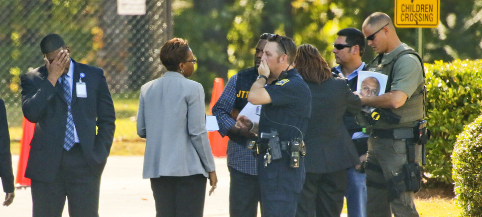 Photo -   Law enforcement gather in front of the chapel at World Changers Church International in College Park, Ga. Wednesday, Oct. 24, 2012, where a church volunteer leading prayer was shot and killed. Authorities were searching for a former church employee suspected in the shooting. (AP Photo/Atlanta Journal-Constitution, John Spink) MARIETTA DAILY OUT; GWINNETT DAILY POST OUT; LOCAL TV OUT; WXIA-TV OUT; WGCL-TV OUT