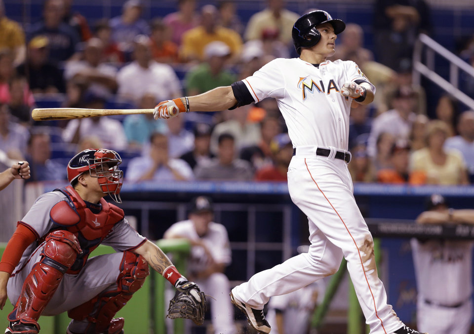 Photo - Miami Marlins' Derek Dietrich, right, watches after hitting a three-run home run as Washington Nationals catcher Jose Lobaton, left, looks on during the fourth inning of a baseball game, Wednesday, April 16, 2014, in Miami. (AP Photo/Lynne Sladky)