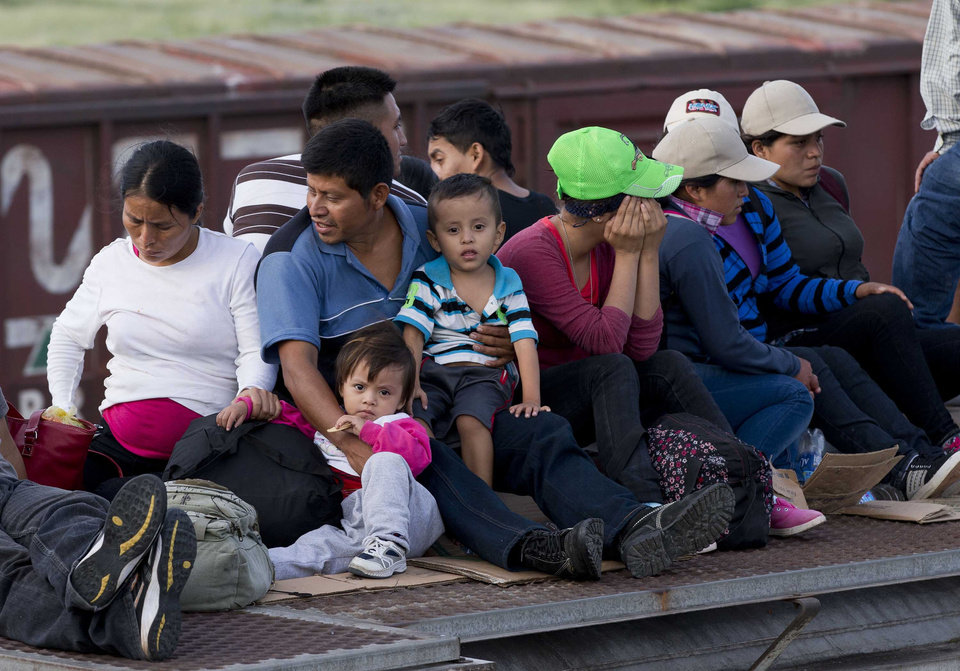 Photo - In this July 12, 2014, photo, Central American migrants ride a freight train during their journey toward the U.S.-Mexico border in Ixtepec, Mexico. The number of family units and unaccompanied children arrested by Border Patrol in the Rio Grande Valley has doubled in the first nine months of this fiscal year compared to the same period last year.  (AP Photo/Eduardo Verdugo)