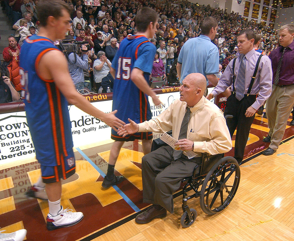 Photo - FILE - In a Saturday, Jan. 10, 2009 file photo, Northern State University Men's Basketball Coach, Don Meyer, shakes hands with a University of Mary player after he got his 903rd win, passing Bobby Knight as the NCAA's winningest coach in men's basketball history, in Aberdeen, S.D. Meyer, one of the winningest coaches in college basketball who came back from a near-fatal car accident and liver cancer before closing out his career, has died in South Dakota. He was 69. (AP Photo/Doug Dreyer, File)