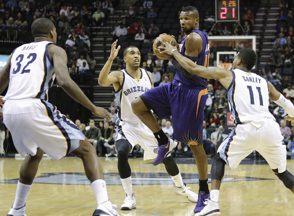 Photo - Phoenix Suns guard Leandro Barbosa, second from right, of Brazil, shoots against Memphis Grizzlies forward Ed Davis (32), guard Courtney Lee and guard Mike Conley (11) in the first half of an NBA basketball game, Friday, Jan. 10, 2014, in Memphis, Tenn. (AP Photo/Lance Murphey)