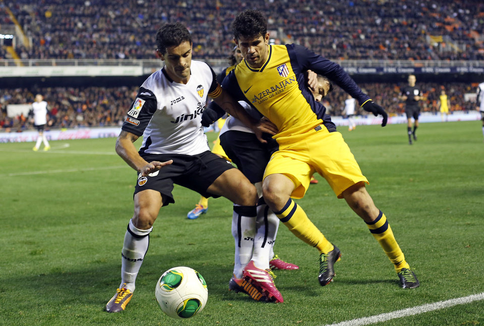 Photo - Atletico de Madrid's  Diego Costa, right,  duels for the ball with Valencia's  Ricardo Costa from Portugal  during their la Copa del Rey soccer match at the Mestalla stadium in Valencia, Spain, Tuesday, Jan. 7, 2014. (AP Photo/Alberto Saiz)