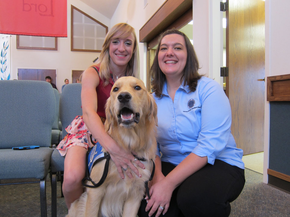 Photo - bold Hannah McGinnis, 19, of Maywood, Ill., and Sherry Bolosan, with Addison, Ill.-based Lutheran Church Charities, pose for a picture with Rufus Comfort Dog after Sunday worship services at St. Mark Lutheran Church in Edmond. Photo by Carla Hinton, The Oklahoman