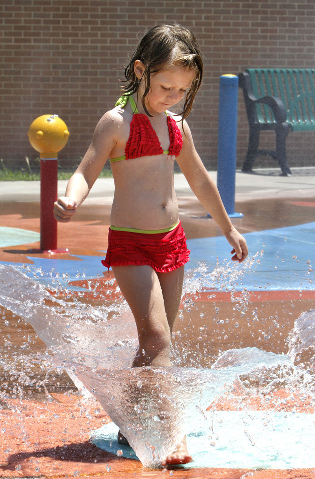 Photo - Wild art. Vanessa Thorn, 4, plays in the water at a splash par in Macklanburg Park at 117 and north McKinley, Monday, June 25, 2012. Photo By David McDaniel/The Oklahoman