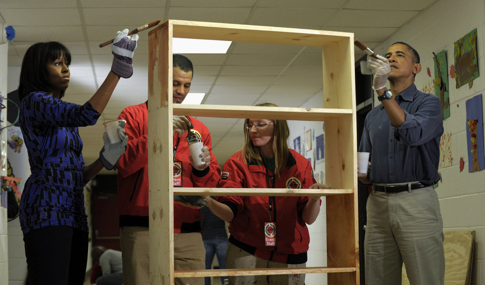 Photo - President Barack Obama and first lady Michelle Obama stain a bookshelf at Burrville Elementary School in Washington, Saturday, Jan. 19, 2013, as the the first family participated in a community service project for the National Day of Service, part of the 57th Presidential Inauguration. (AP Photo/Susan Walsh)