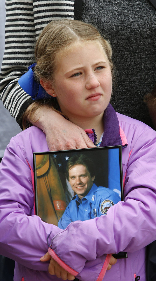 Photo - With her mother's arm resting on her shoulder, Cadence Treece, 7, cradles a photo of her dad, Lt. Wesley Treece, a firefighter with 14 years of service in the Shawnee Fire Department who died of colon cancer in March 2009. He was 42. Lt. Treece was among hundreds of firefighters who responded to the scene in Oklahoma City after the Murrah Federal Building was destroyed in a bomb attack in April 1995. Cadence attended Monday's rally with her brother and mother, Richelle.