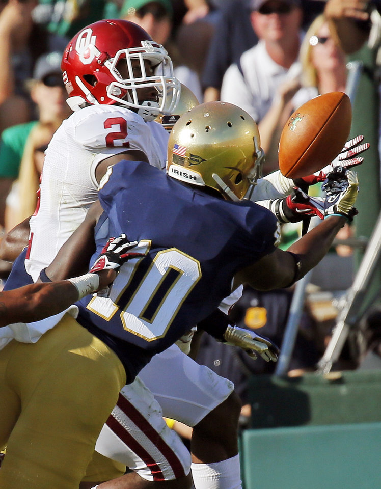 Photo - Oklahoma's Julian Wilson (2) intercepts a pass next to Notre Dame's DaVaris Daniels (10) in the second quarter during a college football game between the University of Oklahoma Sooners (OU) and the Notre Dame Fighting Irish at Notre Dame Stadium in South Bend, Ind., Saturday, Sept. 28, 2013. Photo by Nate Billings, The Oklahoman