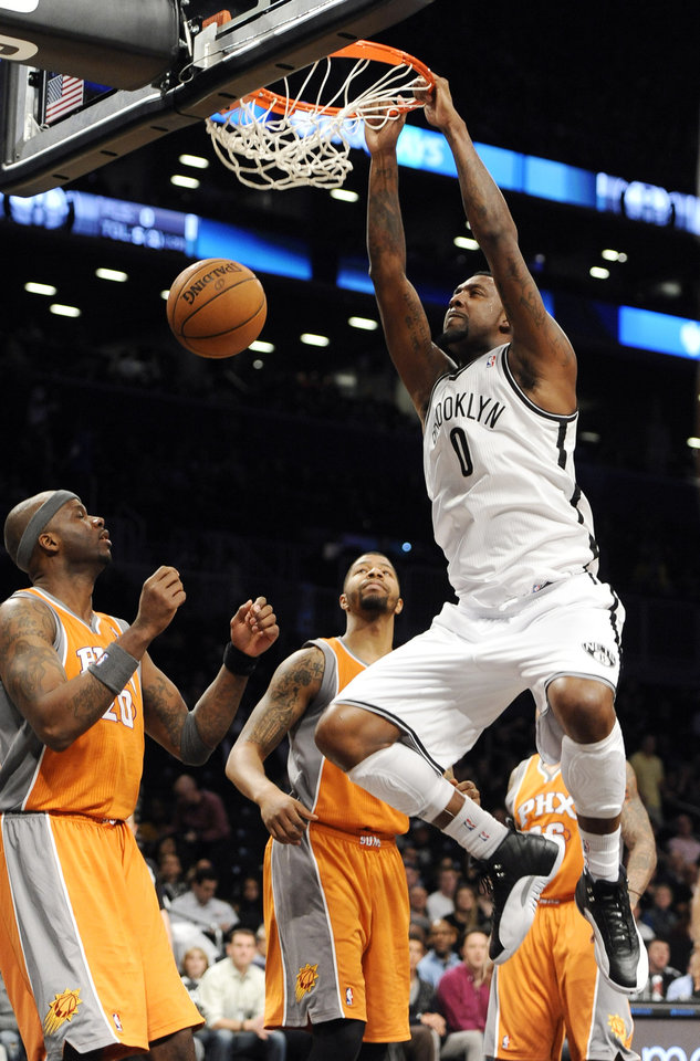 Photo - Brooklyn Nets' Andray Blatche (0) dunks a basket in front of Phoenix Suns' Jermaine O'Neal (20) and Markieff Morris, second from left, in the first half of an NBA basketball game on Friday, Jan., 11, 2013 at Barclays Center in New York. (AP Photo/Kathy Kmonicek)