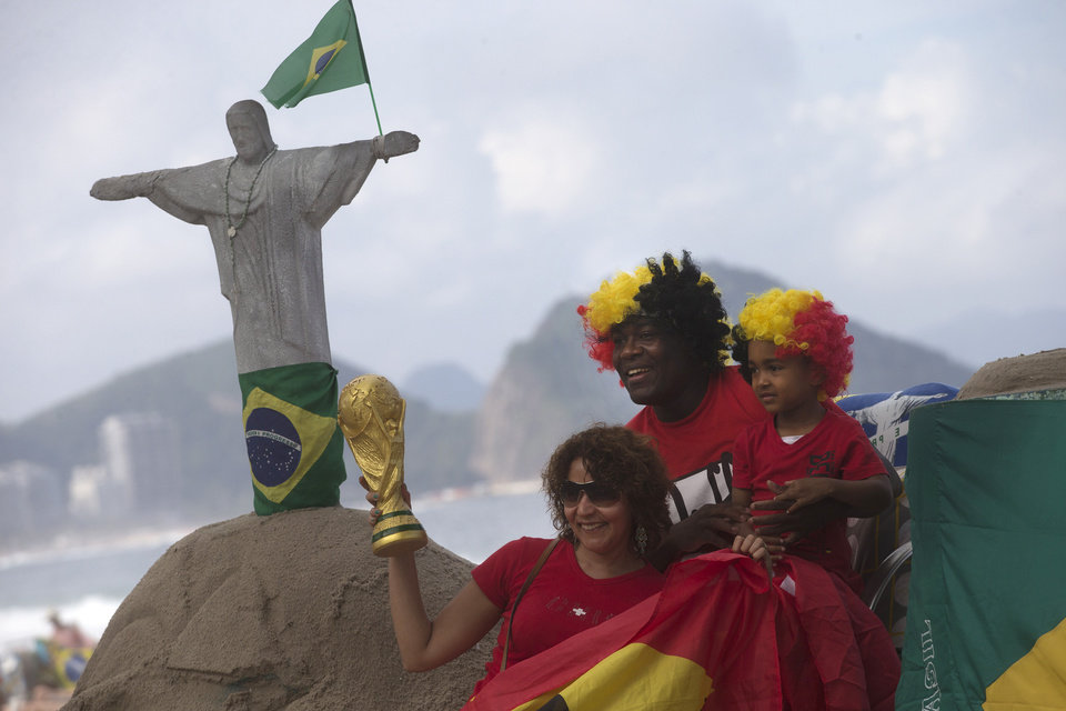 Photo - Soccer fans from Belgium pose for a photo with a replica of a World Cup trophy on Copacabana beach in Rio de Janeiro, Brazil, Wednesday, June 11, 2014. The World Cup soccer tournament starts Thursday. (AP Photo/Silvia Izquierdo)