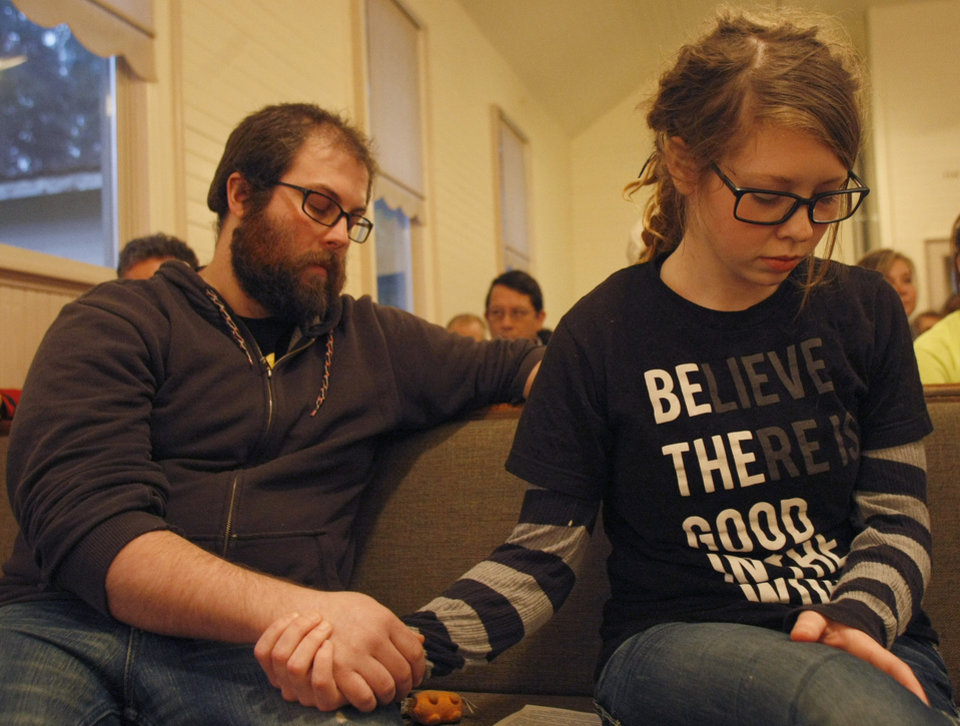 Photo - Community members Ryan and Molly Ray pray for mudslide victims at the Oso Community Chapel Wednesday, March 26, 2014, in Oso, Wash. (AP Photo/The Herald,  Sofia Jaramillo)