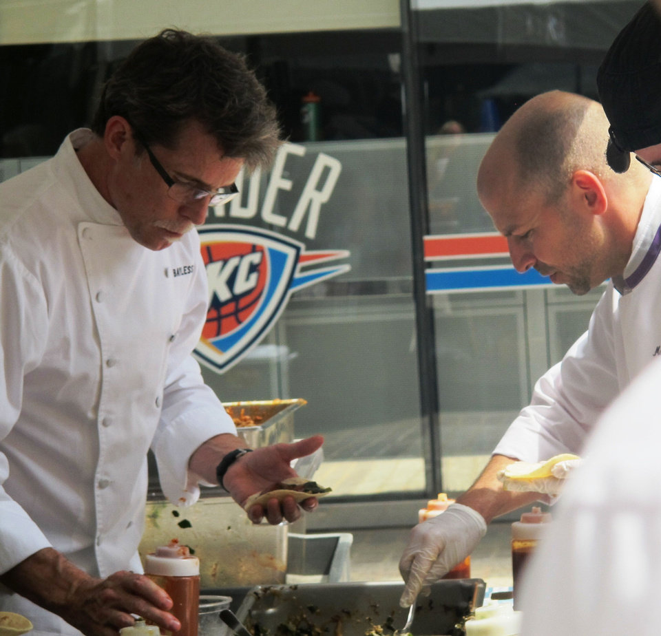 Photo - Chef Rick Bayless, left, and Marc Dunham work the line during the OK Chefs Relief pop-up at Leadership Square on Monday.  DAVE CATHEY - THE OKLAHOMAN