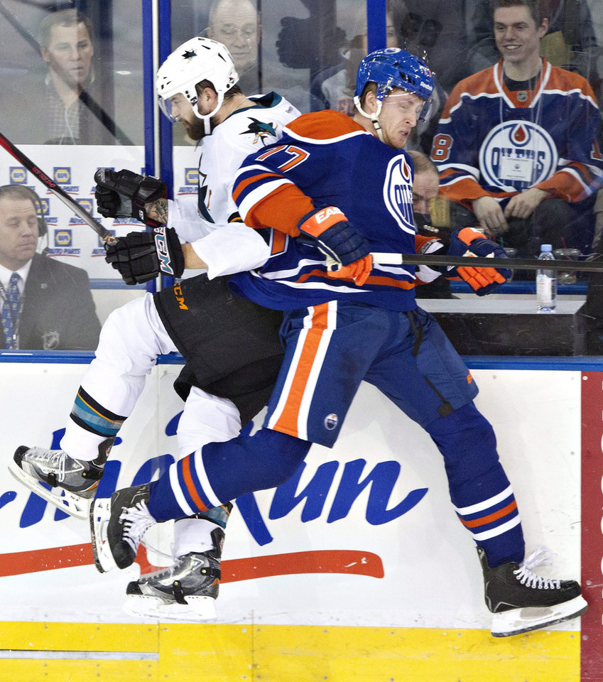 Photo - San Jose Sharks' Brent Burns (88) is checked by Edmonton Oilers' Anton Belov (77) during the second period of an NHL hockey game Wednesday, Jan. 29, 2014, in Edmonton, Alberta. (AP Photo/The Canadian Press, Jason Franson)
