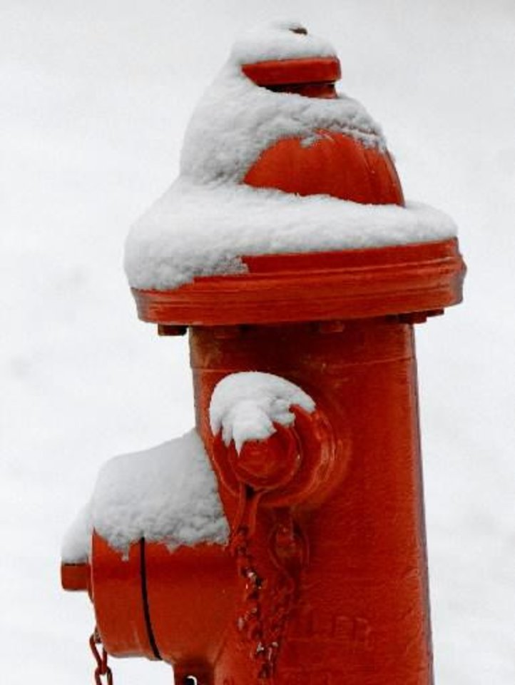 Photo - Snow clings to a fire hydrant after about an inch of snow fell overnight in Edmond, OK, Monday, Feb. 13, 2012. By Paul Hellstern