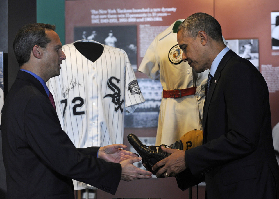 Photo - President Barack Obama is handed Joe DiMaggio's well-worn baseball glove by Baseball Hall of Fame President Jeff Idelson during a tour the Baseball Hall of Fame in Cooperstown, N.Y., Thursday, May 22, 2014. Obama visited the museum to highlight tourism and steps to help spur international visits to the 50 states. Obama said the overall U.S. economy and local businesses will benefit if it isn't a hassle for people from other countries to visit the U.S. and spend money at its hotels, restaurants, tourist destinations and other businesses. An autographed Carlton Fisk Chicago White Sox jersey is behind them. (AP Photo/Susan Walsh)