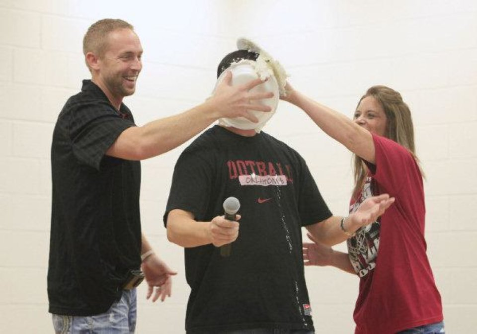 Jason White, left, and Carrie Vaughn, right, PTA president, rub pie in the face of Heritage Trails Elementary School Principal Jason Perez during an assembly Wednesday morning at the school. White was a special guest for the morning. PHOTO BY PAUL B. SOUTHERLAND, THE OKALHOMAN <strong>PAUL B. SOUTHERLAND - PAUL B. SOUTHERLAND</strong>