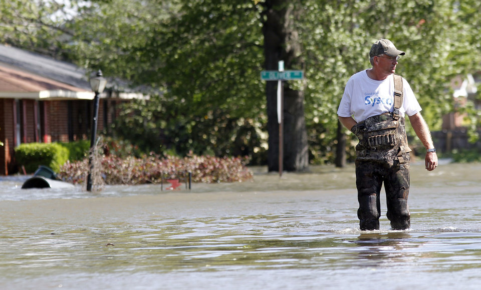 Photo - Clayton Hudson walks down a flooded street as he checks on his cousin's house on Wednesday, April 27, 2011, in West Memphis, Ark. Strong storms hit the South Wednesday for the second straight day. (AP Photo/Mark Humphrey)