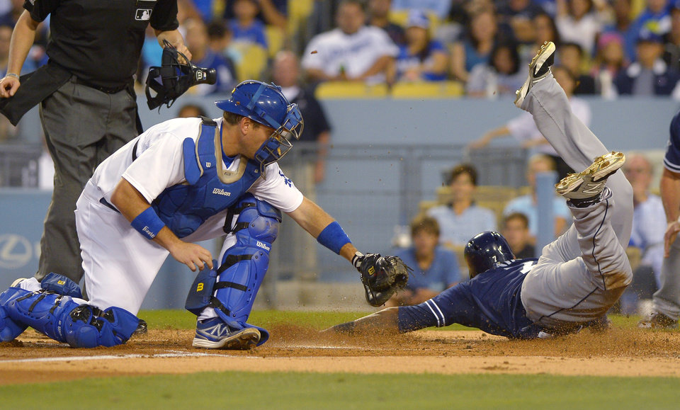 Photo - San Diego Padres' Rymer Liriano, right, scores under the tag of Los Angeles Dodgers catcher A.J. Ellis on a single by Eric Stults and a fielding error by Scott Van Slyke during the second inning of a baseball game, Wednesday, Aug. 20, 2014, in Los Angeles.  (AP Photo/Mark J. Terrill)