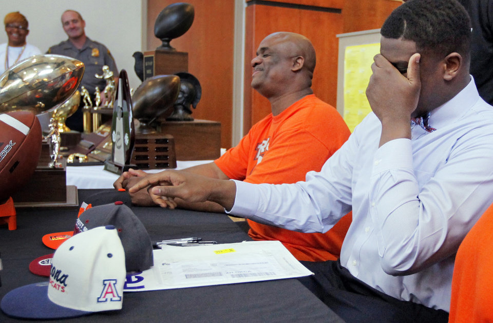 Cayman Bundage jokes around by covering his eyes and pretending to pick between Oklahoma, Oklahoma State and Arizona caps as his father, Clyde Bundage, laughs during the National Signing Day ceremony at Douglass High School in Oklahoma City, Wednesday, Feb. 1, 2012. Bundage signed to play football with the University of Arizona. Photo by Nate Billings, The Oklahoman