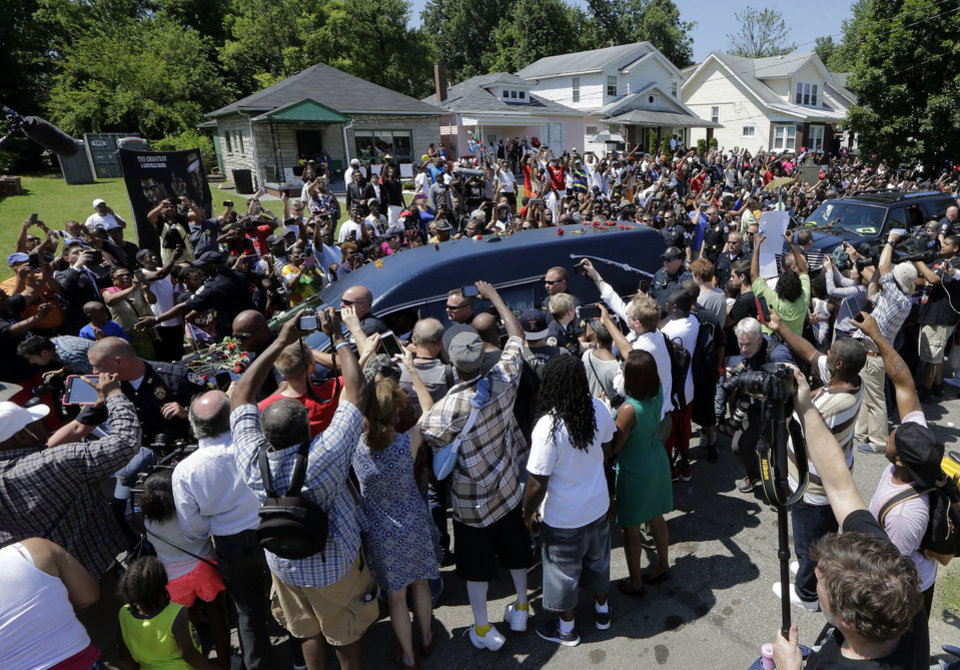 Photo - The hearse carrying the body of Muhammad Ali passes in front of his boyhood home during his funeral procession Friday, June 10, 2016, in Louisville, Ky. Ali's home was the second house from the left. (AP Photo/Mark Humphrey)