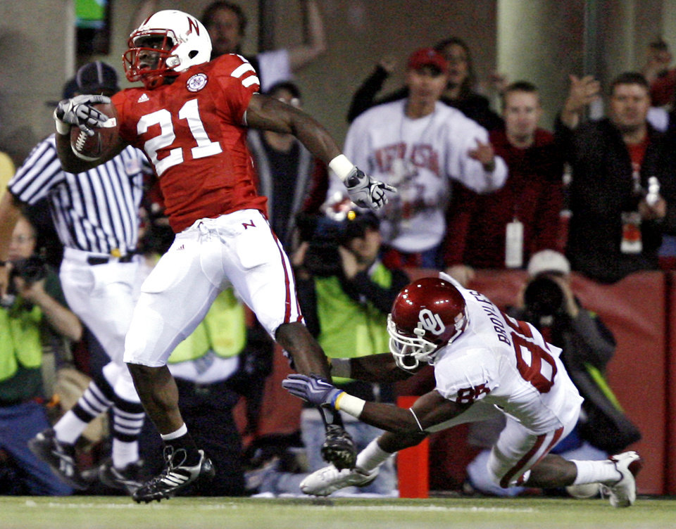 Photo - Nebraska's Prince Amukamara (21) gets past Oklahoma's Ryan Broyles (85) after making an interception during the first half of the college football game between the University of Oklahoma Sooners (OU) and the University of Nebraska Cornhuskers (NU) on Saturday, Nov. 7, 2009, in Lincoln, Neb.