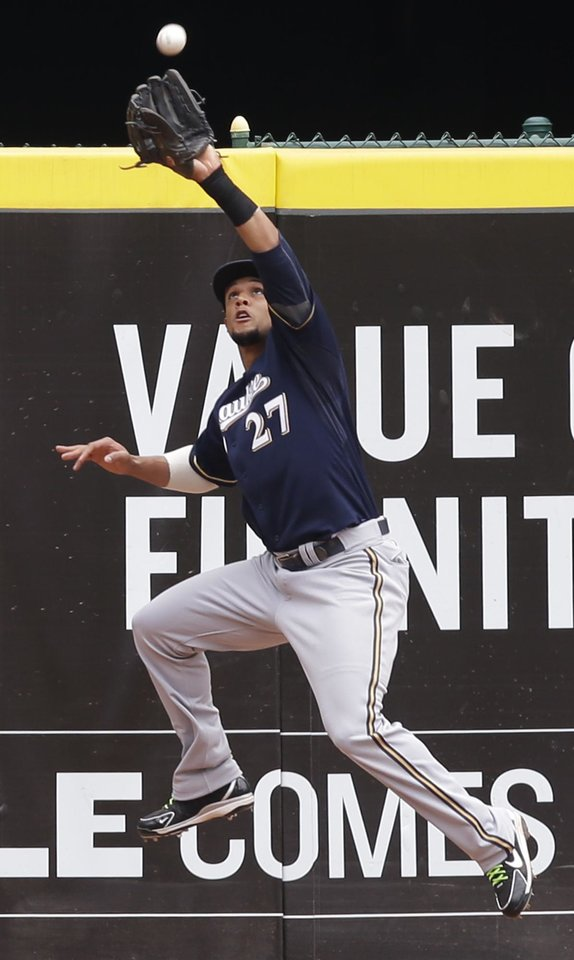 Photo - Milwaukee Brewers center fielder Carlos Gomez catches a fly ball hit by Cincinnati Reds' Jay Bruce in the fourth inning of a baseball game on Sunday, July 6, 2014, in Cincinnati. (AP Photo/Al Behrman)